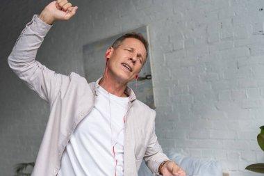 Man in earphones dancing and singing at home