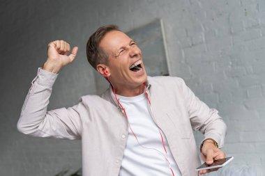 Exited man in earphones dancing in living room