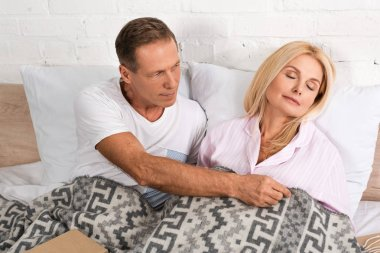 Man covering with blanket sleeping wife in bed