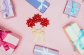 vrchní pohled na vánoční dárkové krabice se stuhami a luky, izolované na růžové