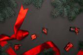 vrchní pohled na vánoční dárkové krabice a červenou stuhu se smrkovými větvemi na černé