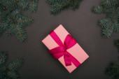 Fotografie Horní pohled na růžové vánoční dárek se smrkovými větvemi na černé