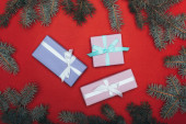 top view of christmas gift boxes with spruce branches on red