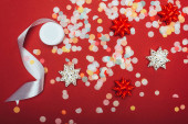 top view of christmas confetti, white ribbon and bows on red