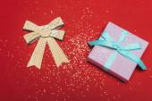Fotografie vrchní pohled na jeden vánoční dárek se zlatou mašlí a konfetami na červené