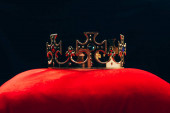 antique golden crown with gemstones on red pillow, isolated on black