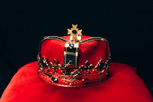 ancient golden crown with gemstones on red pillow, isolated on black