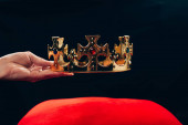 cropped view of woman holding golden crown with gemstones over red pillow, isolated on black