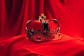 antica corona doro con pietre preziose su stoffa rossa