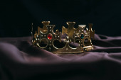 Fotografia corona dorata retrò con pietre preziose su stoffa nera