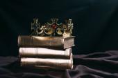 Fotografia antica corona doro con pietre preziose su libri su stoffa nera