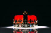 antique red golden crown with gemstones on black
