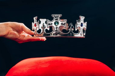 cropped view of woman holding silver crown with gemstones over red pillow, isolated on black