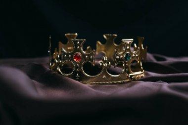 Retro golden crown with gemstones on black cloth stock vector