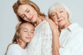 smiling granddaughter, mother and grandmother with closed eyes hugging isolated on grey