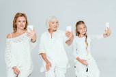 Fotografie Lächelnde Enkelin, Mutter und Großmutter machen Selfies isoliert auf grau