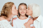 mother and grandmother kissing smiling granddaughter isolated on grey