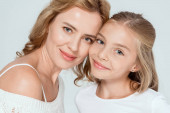 atraktivní matka a usmívající se dcera při pohledu na kameru izolované na šedé