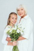 smiling grandmother hugging granddaughter with bouquet isolated on grey