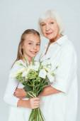 Fotografie Lächelnde Großmutter umarmt Enkelin mit Blumenstrauß