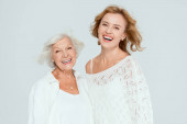 smiling mother and daughter looking at camera isolated on grey