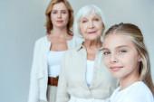Fotografie selektiver Fokus lächelnder Enkelin und Großmutter, Mutter im Hintergrund isoliert auf grau