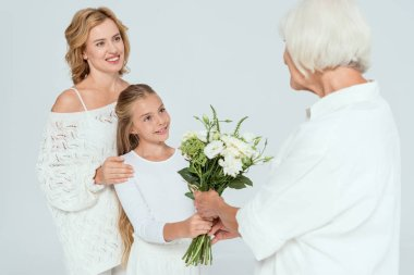 Smiling granddaughter giving bouquet to grandmother isolated on grey stock vector