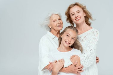 Smiling granddaughter, mother and grandmother hugging isolated on grey stock vector
