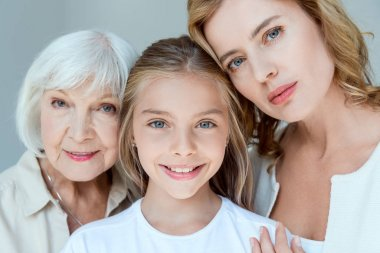 Mother, grandmother and smiling granddaughter looking at camera isolated on grey stock vector