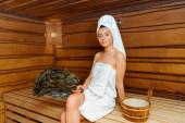 atraktivní žena v ručnících držící březové koště a dívající se na kameru v sauně