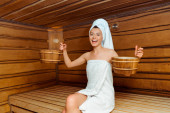 usmívající se a atraktivní žena v ručnících držící vany v sauně