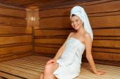atraktivní a usmívající se žena v ručnících při pohledu na kameru v sauně