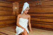 atraktivní žena v bílých ručnících shlíží dolů v sauně