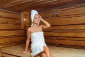 atraktivní a usmívající se žena se zavřenýma očima v ručnících v sauně