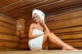 Blick auf eine lächelnde und attraktive Frau in Handtüchern in der Sauna