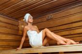 nízký úhel pohledu na usmívající se a atraktivní ženu v ručnících se zavřenýma očima v sauně