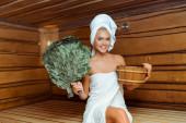 usmívající se a atraktivní žena v ručnících držící vanu a břízové koště v sauně