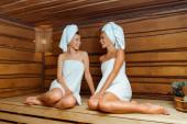 usmívající se a atraktivní přátelé v ručnících při pohledu na sebe v sauně