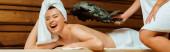 panoramatický záběr ženy bít svého přítele s březovým koštětem v sauně