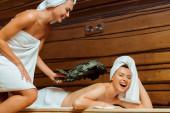 usmívající se a atraktivní žena bít svého přítele s březovým koštětem v sauně