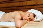 atraktivní žena v ručnících se zavřenýma očima ležící v sauně