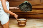 oříznutý pohled na ženu v ručníku držící vanu a břízový koště v sauně