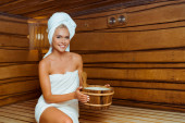 atraktivní a usmívající se žena v ručnících drží dřevěné umyvadlo v sauně