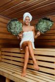 atraktivní a usmívající se žena v ručnících držící březová košťata v sauně
