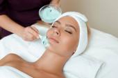 vista ritagliata di cosmetologo applicare maschera viso su attraente donna in spa