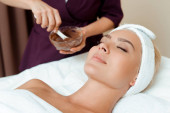 cropped view of cosmetologist holding bowl with face mask and attractive woman lying in spa
