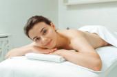 vonzó és mosolygós nő fekszik masszázsasztalon spa