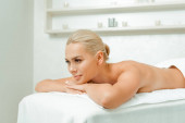 attractive and blonde woman lying on massage table in spa