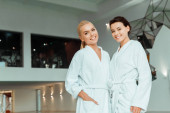 Photo attractive and smiling friends in white bathrobes looking at camera in spa