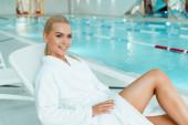 attraktive und lächelnde Frau im weißen Bademantel, die im Wellnessbereich wegschaut